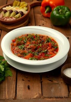 Gebratenes lammfleisch in tomatensauce mit paprika, mit kräutern garnierte tomate