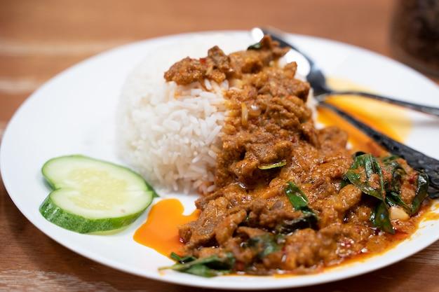 Gebratenes lammfleisch mit currypaste auf dem gekochten reis