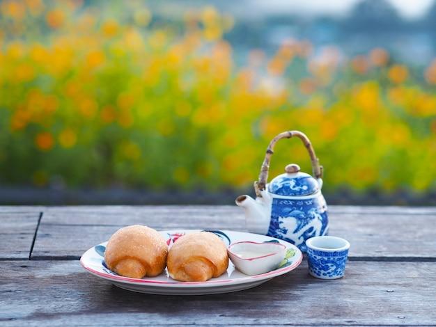 Gebratenes mantou mit kondensmilch und chinesischem tee auf holztisch im freien.