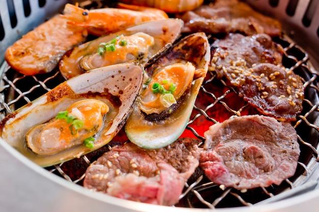 Gebratenes mischfleisch und meeresfrüchte auf dem bbq-grill beim braten.