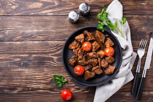 Gebratenes oder gedämpftes rindfleisch mit tomaten