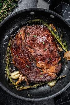 Gebratenes rib-eye-steak, ribeye-rindfleisch in einer pfanne auf schwarzem tisch. draufsicht.