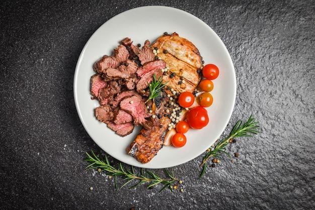 Gebratenes rindersteakfilet und schweinekoteletts mit kraut und gewürzen dienen mit gemüse auf weißer platte - gegrillte rindfleischscheibe auf schwarzem hintergrund