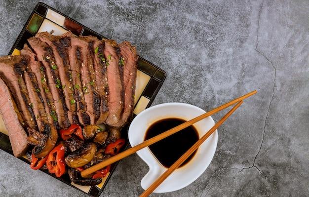 Gebratenes rindfleisch mit sojasoße auf platte, draufsicht.