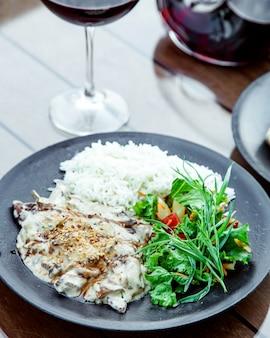 Gebratenes rindfleisch unter pilzsauce mit reis