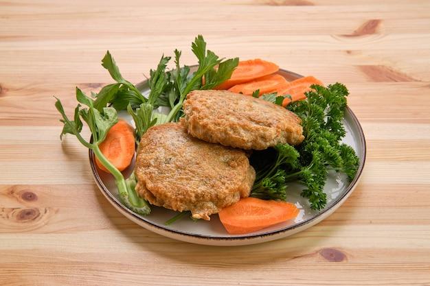 Gebratenes rindfleischkotelett beim panieren mit frischer karotte