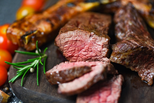 Gebratenes rindfleischsteakfilet mit kraut und gewürzen diente mit gemüse auf hölzernem brett - gegrillte rindfleischfleischscheibe auf schwarzem hintergrund