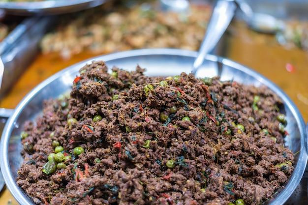 Gebratenes scharfes würziges fleisch mit thailändischem paprika und kraut für verkauf am thailändischen straßenlebensmittelmarkt oder am resta