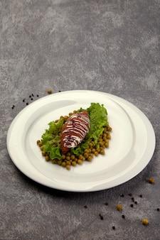 Gebratenes schnitzel mit grünen erbsen