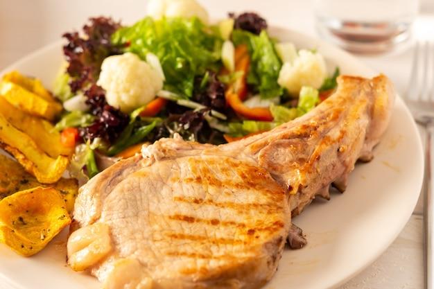 Gebratenes schweineentrecôte am knochen mit gedünsteten kürbisstücken und salat in einem teller nahaufnahme, grüner salat mit blumenkohl und napa-kohl, paprika und gewürzen