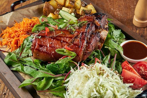 Gebratenes schweinefleisch knöchelbein in bier und honig mit tomaten, kohl und kartoffeln. traditionelles deutsches bieressen.