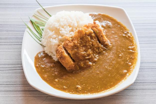 Gebratenes schweinefleisch mit curryreis