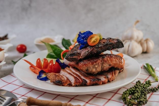 Gebratenes schweinefleisch mit gebratenem chili gebratene zwiebel und minze in einem weißen teller.