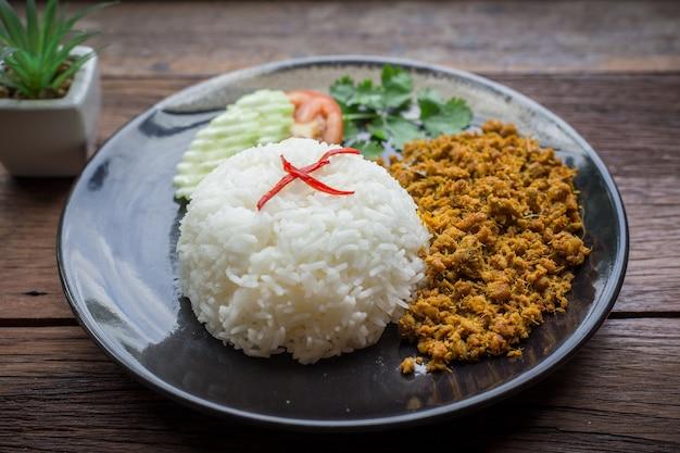 Gebratenes schweinefleisch mit gelber currypaste über reis ist auf einem schwarzen teller und einem braunen holz als hintergrund