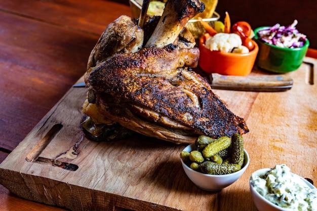 Gebratenes schweinefleisch mit gemüse auf holztisch