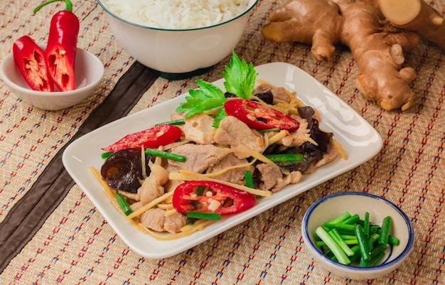 Gebratenes schweinefleisch mit geschnittenem ingwer, serviert mit reis auf thai mat - thai culture food
