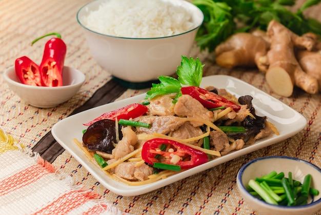 Gebratenes schweinefleisch mit geschnittenem ingwer, serviert mit reis auf thai mat - thai-essen