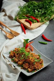 Gebratenes schweinefleisch mit getrocknetem chili und salz auf dunklem hintergrund