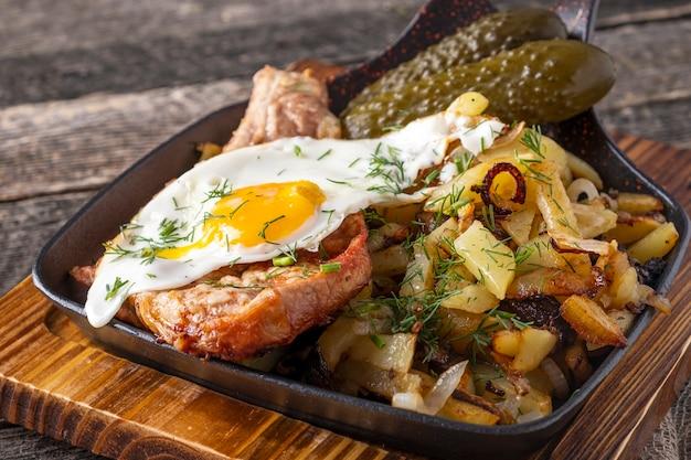 Gebratenes schweinefleisch mit kartoffeln und ei.