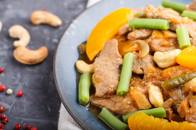 Gebratenes schweinefleisch mit pfirsichen, acajoubaum und grünen bohnen, abschluss oben, draufsicht.