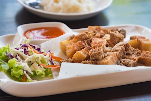 Gebratenes schweinefleisch mit salz in einer weißen platte