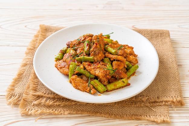 Gebratenes schweinefleisch und rote curry-paste mit stachelbohne umrühren. asiatischer essensstil