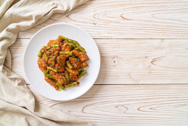 Gebratenes schweinefleisch und rote curry-paste mit stachelbohne umrühren