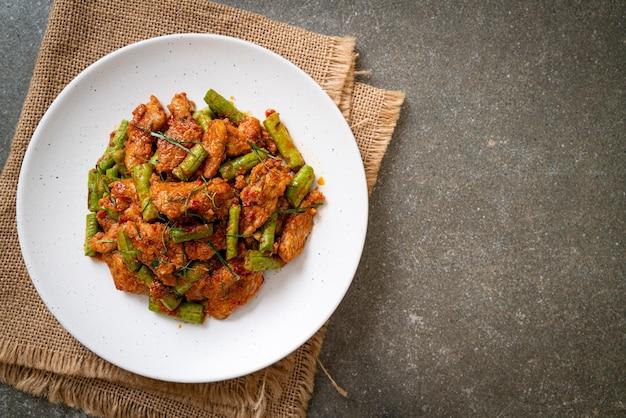 Gebratenes schweinefleisch und rote curry-paste mit stachelbohnen nach asiatischer art umrühren