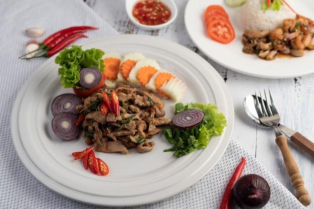 Gebratenes schweinefleischbasilikum auf einem weißen teller mit karotten, gurken und zwiebeln umrühren.
