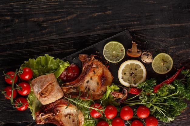 Gebratenes schweinekotelett auf einem schwarzblech mit gewürzen, kräutern und tomaten.