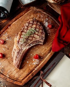 Gebratenes steakstück verarbeitet mit gewürzen auf einem hölzernen brett