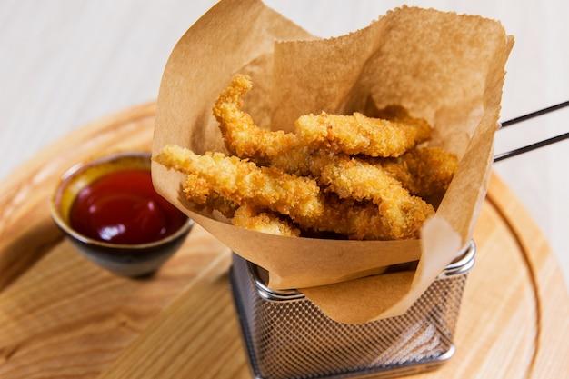 Gebratenes stück huhn im metallkorb auf holztisch in einem restaurant. fast food