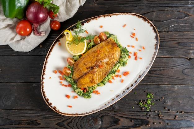 Gebratenes tealapia-fischsteak mit spinatpüree und pesto, garniert mit zitrone.