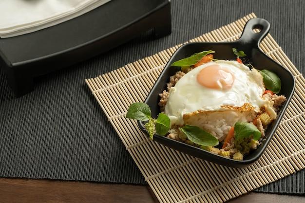 Gebratenes thai-basilikum mit gehacktem schweinefleisch, karotten und baby corns, mit spiegelei und frischem thai-basilikum in einer schwarzen kleinen pfanne auf bambus-tischset, grauem tischset, braunem holztisch sortieren. speicherplatz kopieren