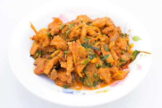Gebratenes wildschwein mit rotem curry nach thailändischer art enthält mit grünem pfeffer heiliges basilikum fingerwurzel