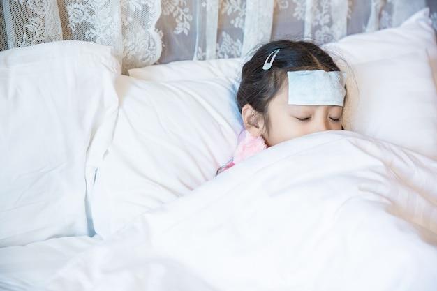 Gebrauchfleckfleck des kleinen mädchens kranker und schlaf auf bett mit weißer decke