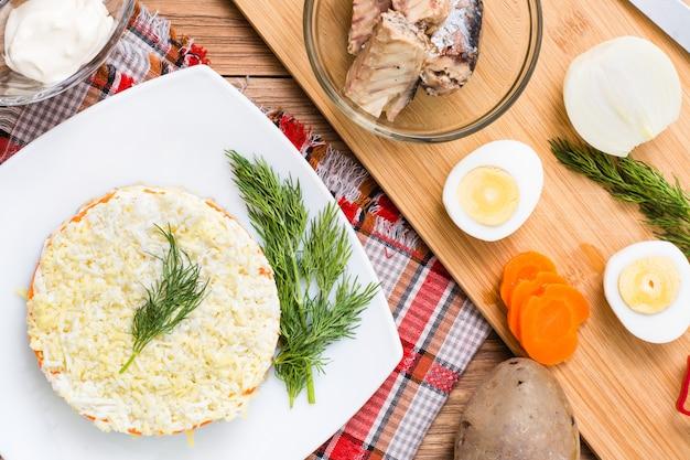 Gebrauchsfertiger russischer teller - mimoza salat. zutaten zum kochen, ansicht von oben