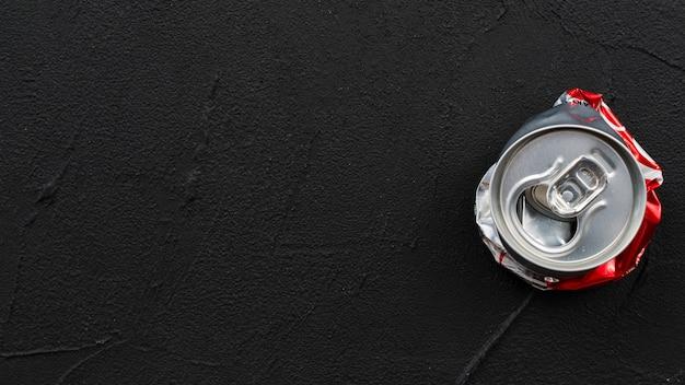 Gebrauchte abgeflachte dose auf schwarzem hintergrund platziert