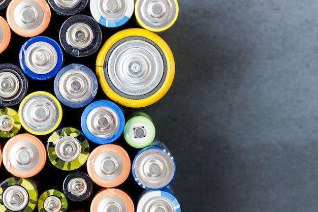 Gebrauchte alkalibatterien unterschiedlicher größe auf schwarzem hintergrund