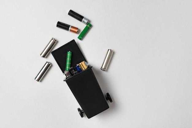 Gebrauchte batterien im behälter auf weißem hintergrund. umweltverschmutzung durch giftigen hausmüll