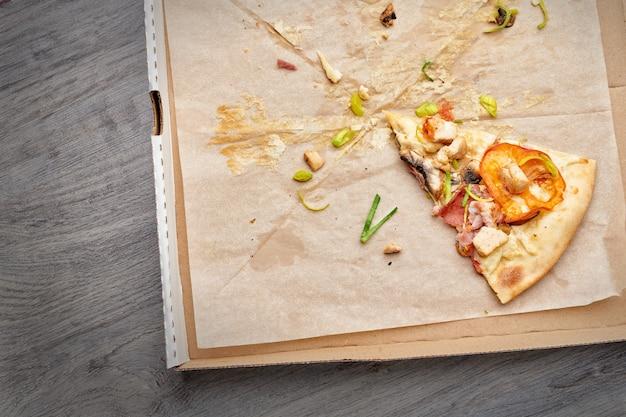Gebrauchte geöffnete pizzaschachtel mit stück pizza, flecken und krümel innen auf hölzernem tischhintergrund. draufsicht