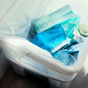Gebrauchte gesichtsmasken in einem kontaminierten mülleimer