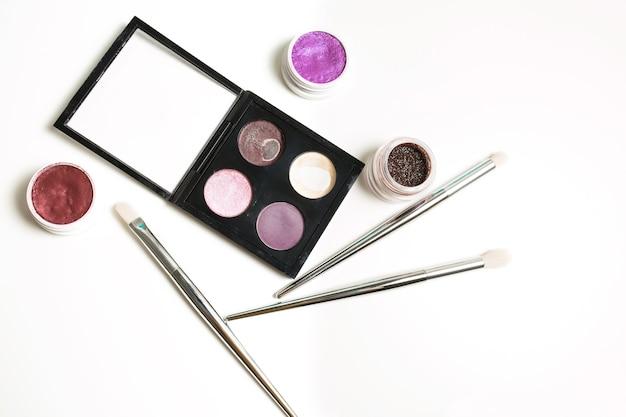 Gebrauchte make-up-palette, pigment, creme-lidschatten und professionelle pinsel auf weißem hintergrund