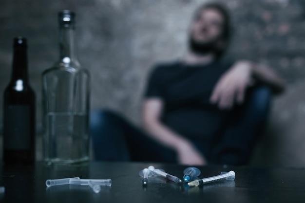 Gebrauchte medizinische ausgepackte spritzen, die auf dem tisch liegen, während freak sitzen