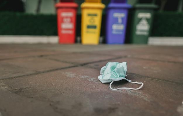 Gebrauchte medizinische gesichtsmaske auf dem bürgersteigboden auf unscharfem papierkorb oder müll entsorgen.