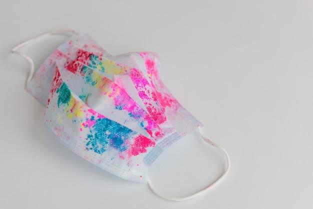 Gebrauchte medizinische gesichtsmaske mit hellen bunten flecken aus holi-farben, auf weißem hintergrund, nahaufnahme. konzept, das indische happy holi festival während der coronavirus-pandemie zu feiern. platz kopieren.