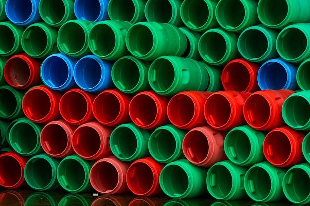 Gebrauchte plastikfässer. blaue, grüne und rote plastiktrommel. gestapelt von leerem tank in der lebensmittelfabrik, der auf recycling und wiederverwendung wartet. rohstoffbehälter in der lebensmittelindustrie.