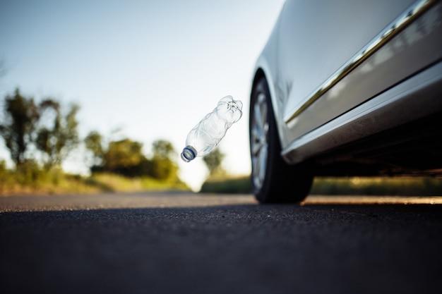 Gebrauchte plastikflasche, die aus dem autofenster auf die straße fällt.