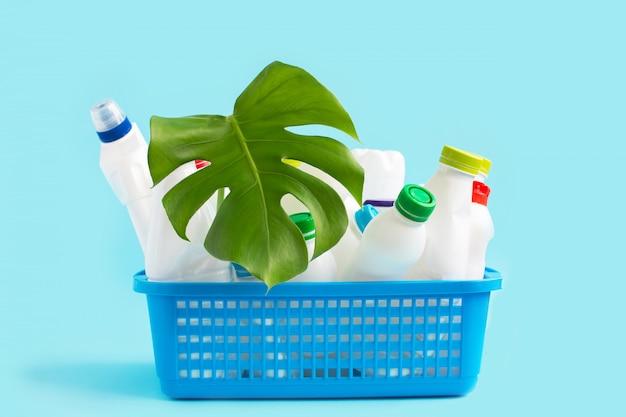 Gebrauchte plastikflaschen mit verschluss und grünem blatt im korb zum recycling.