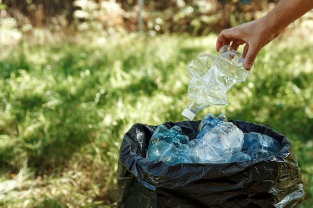 Gebrauchte plastikflaschen werden zum recycling in schwarzen beuteln aufbewahrt.
